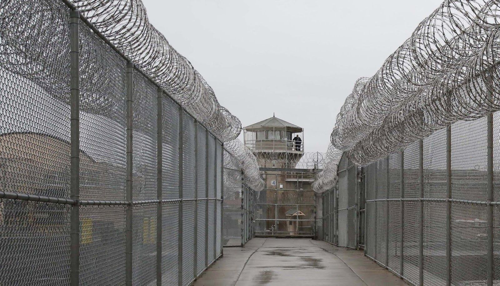 A colored photograph of Washington State Penitentiary's watch tower from the outside, as seen down a concrete corridor. High fences topped with barbed wire line each side of the corridor.