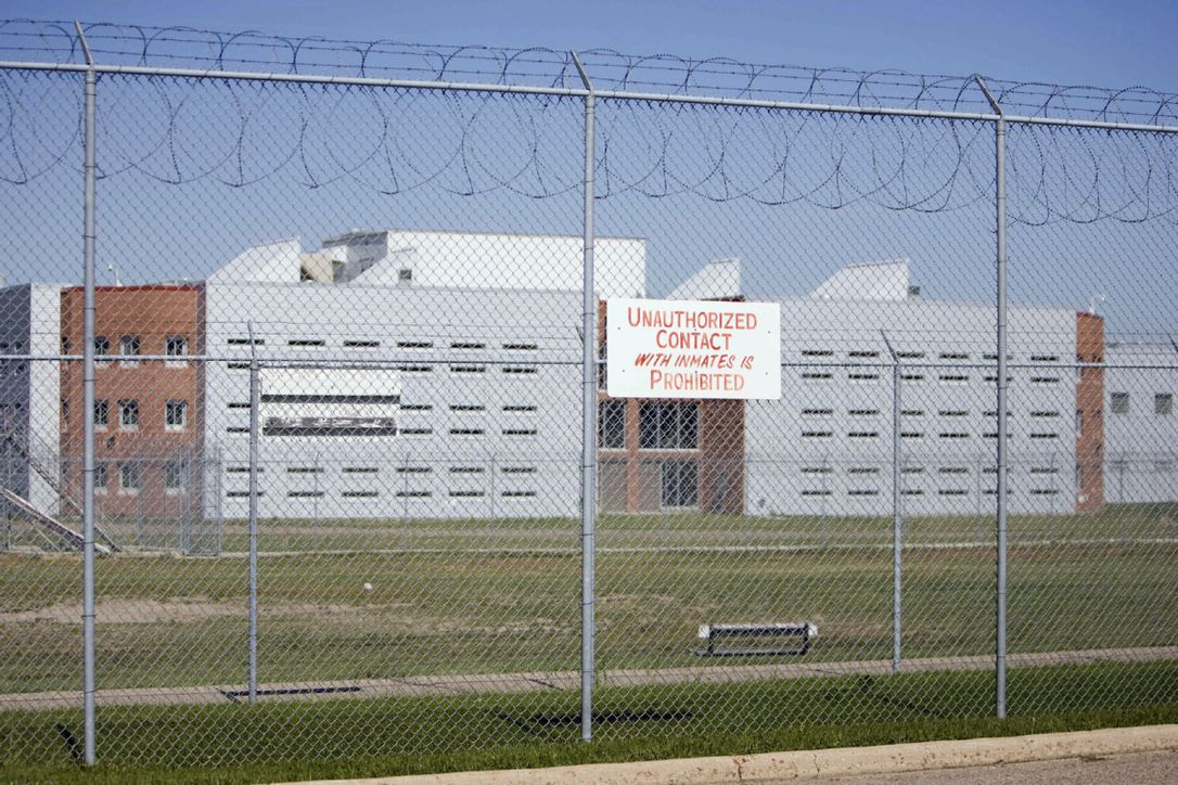 """The Regina Provincial Correctional Centre behind a barbed wire fence with a sign on it saying """"Unauthorized contact with inmates is prohibited"""""""