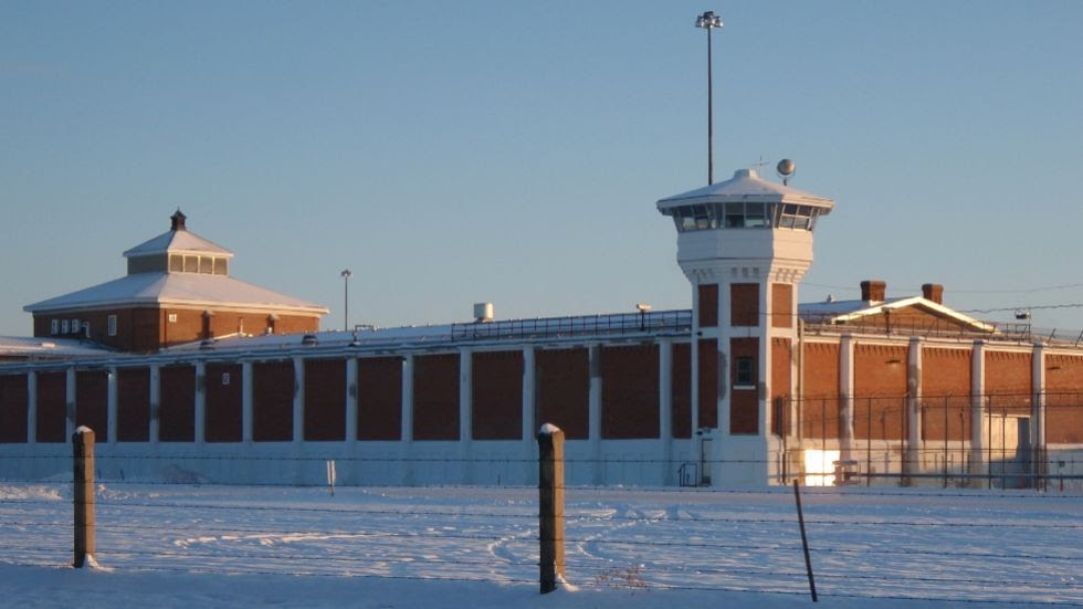 A wintertime image of the Saskatchewan Penitentiary. The brown walls are interspersed with white columns, and there are two towers at either end of the building. A barbed wire fence surrounds the property.