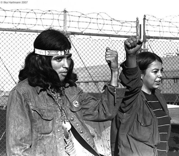 An Indigenous man and woman stand with fists raised in front of a barbed wire fence. They are involved in the occupation of Alcatraz Island, one of the many actions of the American Indian Movement.