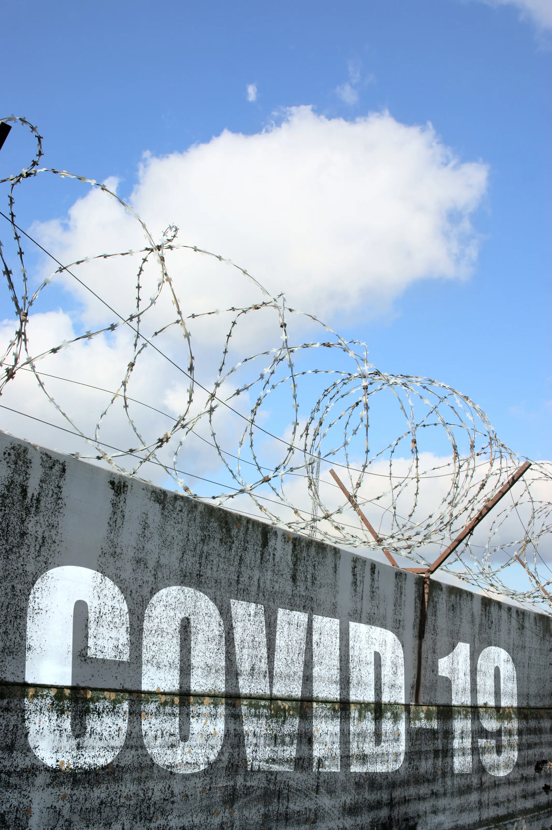 "A concrete wall with ""COVID-19"" in big letters. Barbed wire is at the top of the wall."